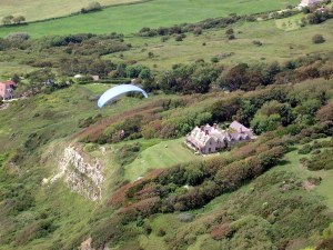 Photo of a paraglider flying near a large house atop a coastal cliff