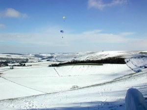 Photo of paragliders flying above snowscape
