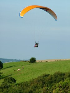 Photo of a two-place paraglider flying above a hillside