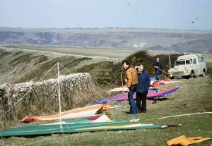 Roly, Peter T, and Roly's mum with flat-rigged hang gliders behind the stone wall at Kimmeridge in 1979