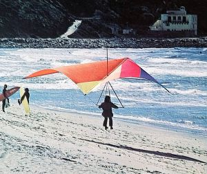 Danny Bostwick lands on the beach in 1974 by Leroy Grannis