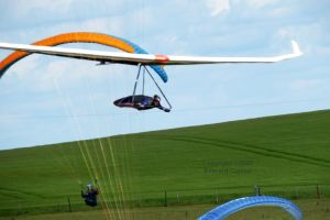 Paragliders and a hang glider flying at Mere, Wiltshire, UK, in June 2020