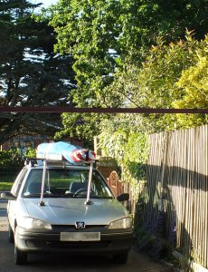 Car in yard with hang glider on roof rack