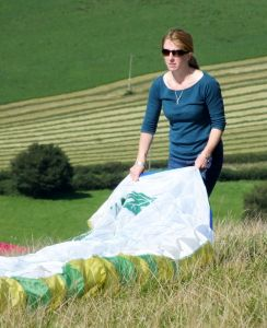 Female paraglider pilot folding wing in 2015