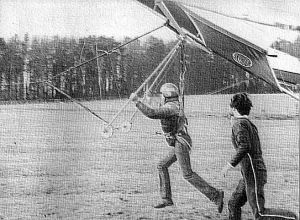 Keith Cockroft hang glider tow by quad with Tony Webb running alongside in 1985
