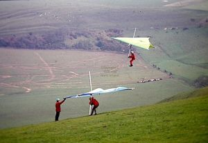 Roly Lewis-Evans waits to launch in a hang glider while Ron Smith passes in front